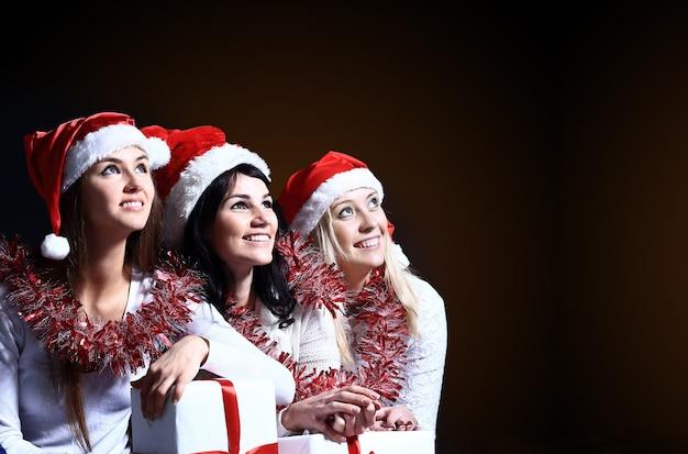 Девочки с новогодним подарком на темном фоне