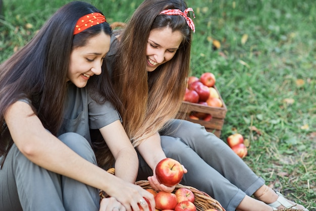 Girls with apple in orchard