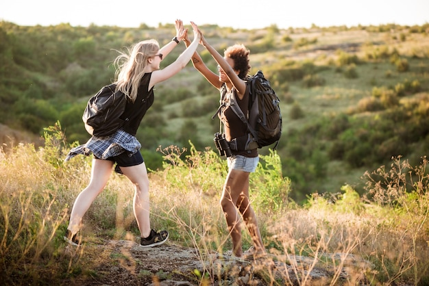Girls with backpacks smiling, giving highfive, traveling in canyon