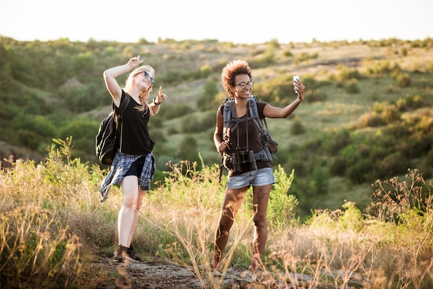 Girls with backpacks smiling, making selfie, traveling in canyon