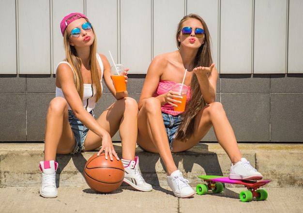 Girls with basketball and skateboard and drinking juice.