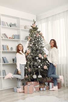 クリスマスのおもちゃを持つ女の子。家にいる女性。姉妹たちは休暇の準備をしています。