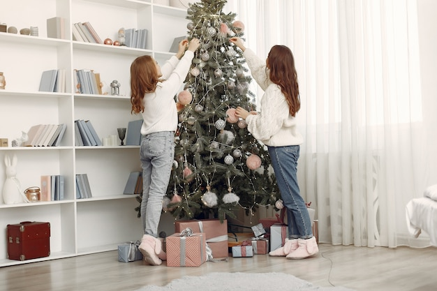 Girls with christmas toys. women at home. sisters are preparing for holidays.