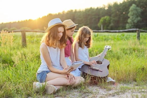 자연에 클래식 기타와 소녀. 잔디밭에서 휴식을 취하는 어린이, 기타 연주 배우기, 노래 부르기, 여름 초원 배경에 일몰