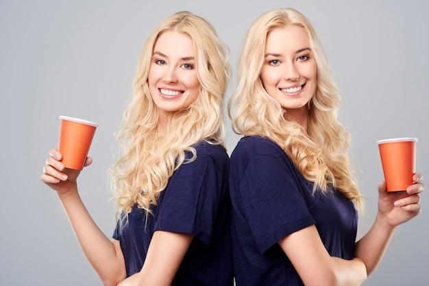 背中合わせに立っているカップを持つ女の子