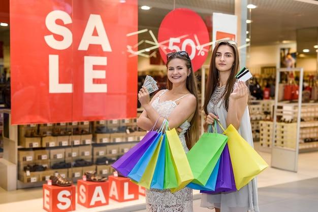 Девушки с долларами и кредитными картами делают покупки в торговом центре