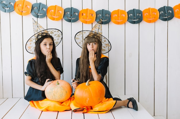Girls with halloween pumpkins closing mouth with hand
