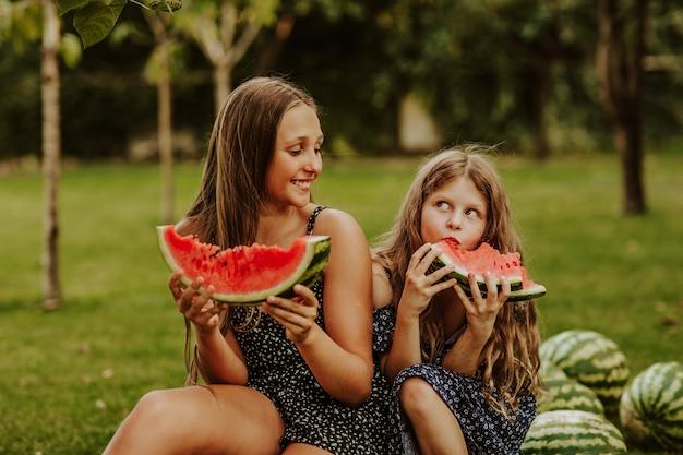 夏のドレスを着た長い髪の女の子が、たくさんのスイカの上に座って、そのスライスを食べています。