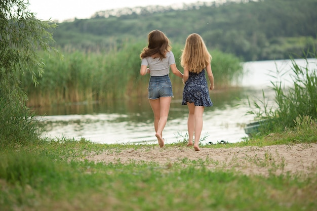 Girls with long hair running to the lake, tourists, outdoor activities