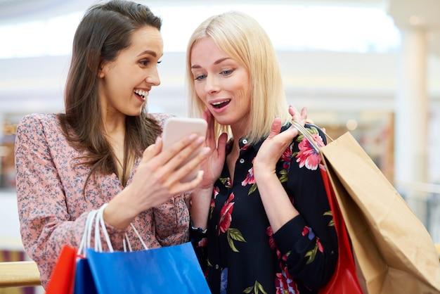 ショッピングの次の方向を選択する携帯電話を持つ女の子