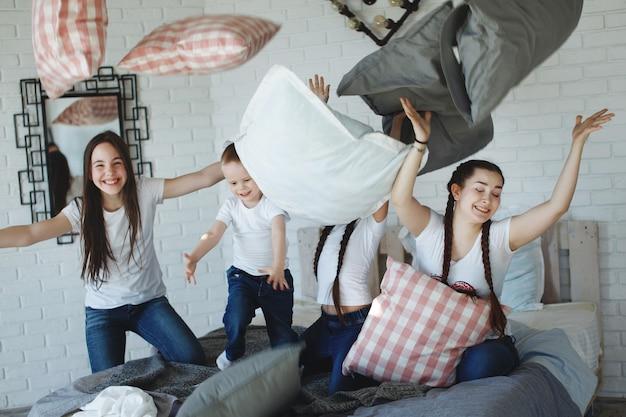 おさげ髪の女の子と弟、白いtシャツとジーンズの家族がベッドの枕で遊んでいます。幸せな家族の概念。