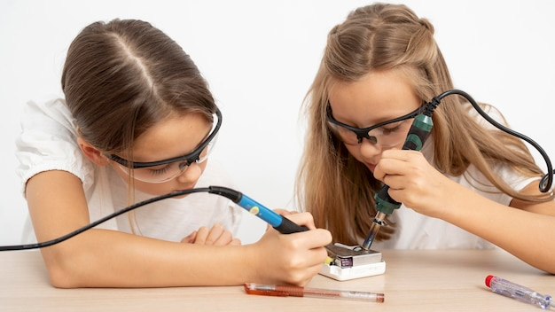 Girls with protective glasses doing science experiments