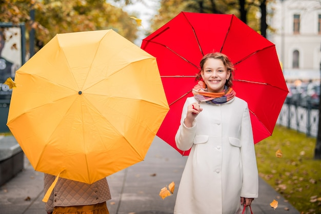 Girls with red and yellow umbrellas walking towards each other on the autumn street of the city. dry fallen leaves on the road.