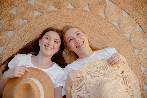 Girls with straw hat dreaming and smiling. girl is dreaming about summer holidays. top horizontal view. health and happiness concept copyspace