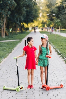 Girls with their push scooters holding each other's hand in the park