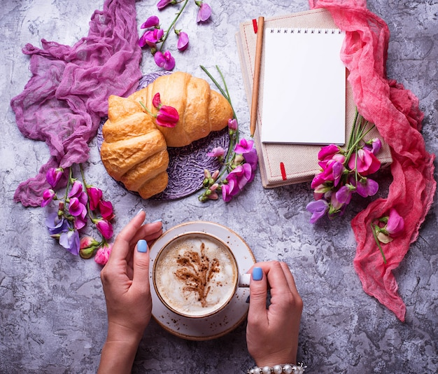 Girls workplace. coffee, croissants, flower and notebook. top view