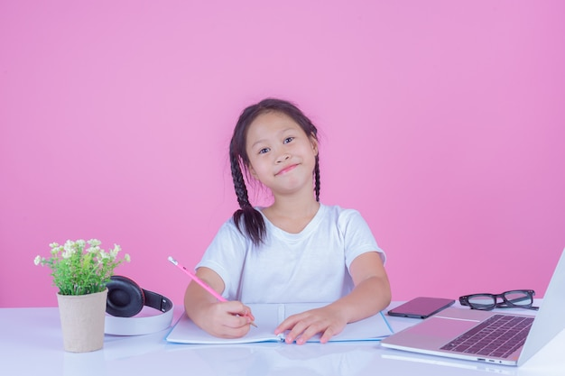 Girls write books on a pink background.