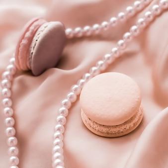 여성스러운 베이커리 및 브랜딩 개념 실크 배경에 달콤한 마카롱과 진주 보석 파리 세련된 보석 프랑스 디저트 음식과 케이크 마카롱 고급 제과 브랜드 휴가 선물