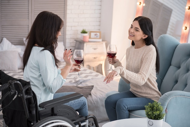Девчачьи вечера. счастливая женщина-инвалид и друг пьют вино и болтают