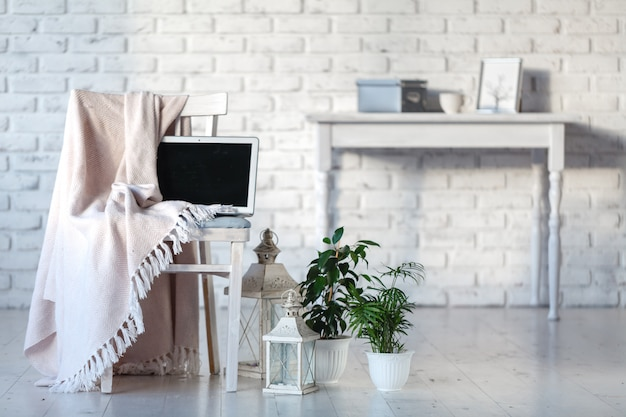 Рабочий стол девчушки офис с пустой белый экран ноутбука, цветы, кофе, смартфон и различные офисные инструменты. макет