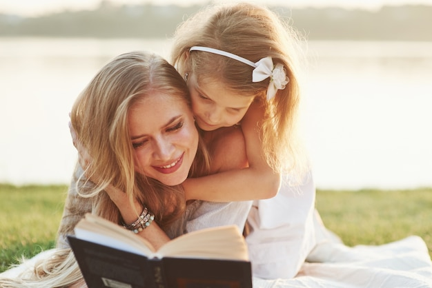 Girly는 그렇게 빨리 읽으려고합니다. 엄마와 딸 배경에서 호수와 잔디에 누워 화창한 날에 책을 읽고.