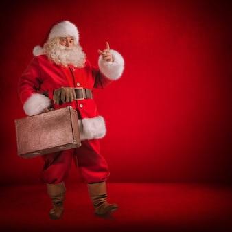 Санта-клаус, стоящий с сумкой для путешествий с gits