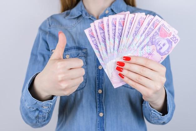 Дайте законопроект, налоговый кредит, процентный ломбард, заработайте банкомат инвестора, инвестора, людей, человека, концепции экономики долга. обрезанное крупным планом фото женских рук с красным маникюром, держащего деньги, изолированный фон