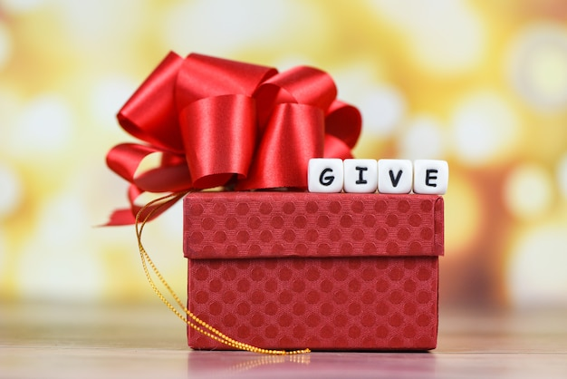 Give gift  a gift box present wrapped with red ribbon