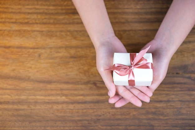 Give a gift on wooden background, top view