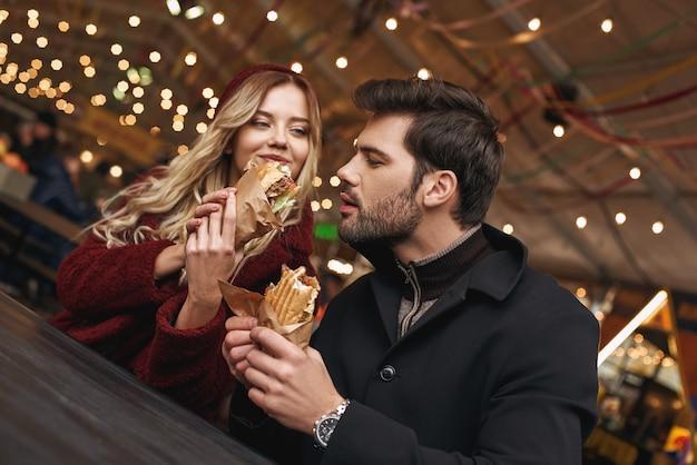 나 좀 줘. 젊은 부부는 길거리 음식 시장에서 샌드위치를 먹고 있다. 추운 계절. 푸드코트에서 식사를 하고 있는 커플의 클로즈업 사진