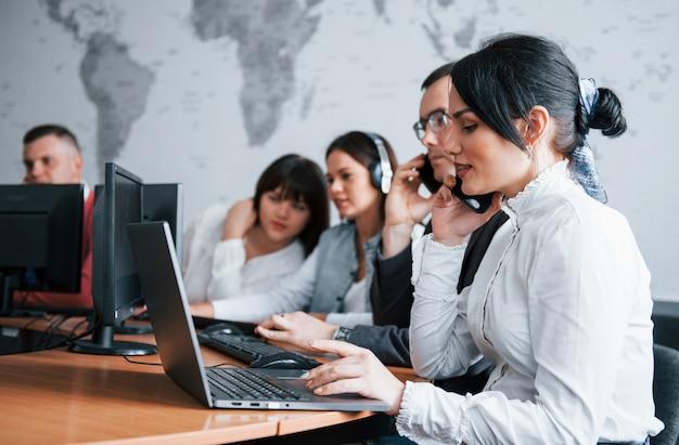 少しお待ちください。解決策を見つけます。コールセンターで働く若者たち。新しい取引が来ています