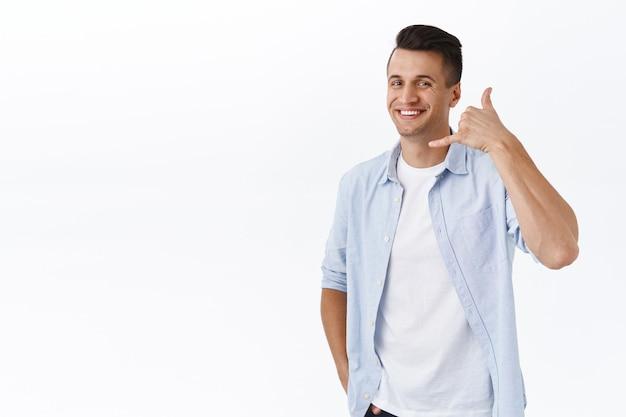 電話してください。顔の近くに電話のサインを示し、彼のサービスを促進するように笑っているハンサムなスタイリッシュな大人の男性の肖像画、あなたが話す必要がある場合に連絡先番号を与える、白い壁に立っている