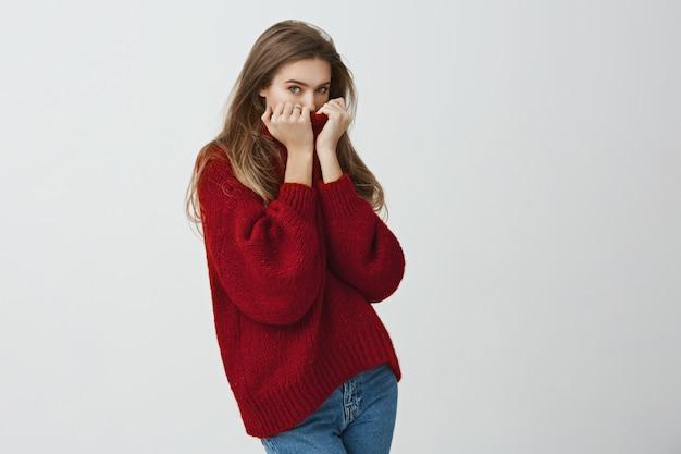 ウォームアップするために寄り添ってください。立っている間ちらっと見えるセーターの襟に顔を隠してかわいいかっこいいヨーロッパの女性の肖像画。ヒーターが壊れて女の子がフリーズする