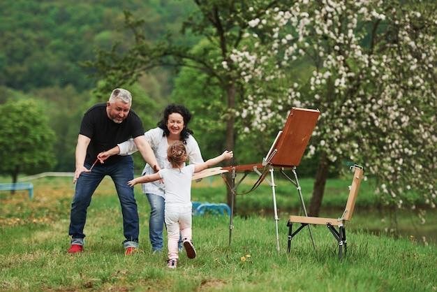 抱きしめて。祖母と祖父は孫娘と屋外で楽しんでいます。絵画の構想