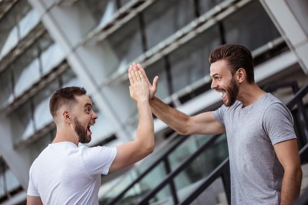 Дай пять! два счастливых возбужденных современных бородатых лучших друга в повседневной одежде веселятся и болтают вместе на открытом воздухе.
