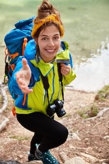 手を貸して!満足している女性の行楽客の垂直ショットは、丘を登ろうとし、ターコイズブルーの湖の近くでポーズをとって、カメラで手を伸ばします
