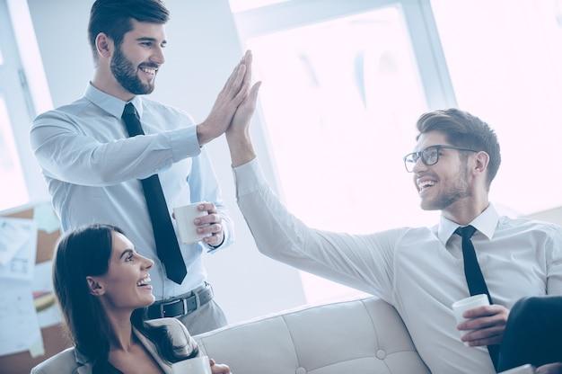 ハイタッチしてください!彼らの美しい同僚とオフィスでソファに座っている間ハイタッチを与え、笑顔でコーヒーカップを保持している2人のハンサムな男