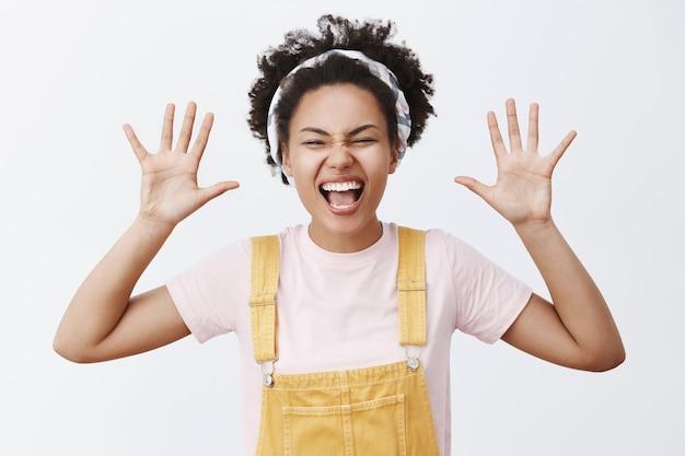 ハイタッチをください。黄色の流行のオーバーオールとヘッドバンドで、手のひらを上げて、嬉しそうに笑って、素晴らしい気分で、魅力的なのんきで幸せなアフリカ系アメリカ人の女子学生の肖像画