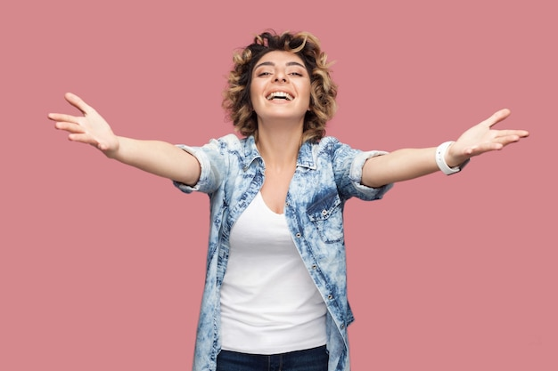 ハグして。抱きしめるために腕を上げて立って、歯を見せる笑顔でカジュアルな青いシャツを着た巻き毛の幸せな若い女性の肖像画。ピンクの背景に分離された屋内スタジオショット