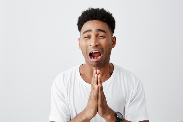 Give me one more try, please. young funny unhappy dark skinned man with afro hairstyle in casual white t shirt pressing palms together with sad expression, crying for forgiveness.