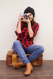 Give me a smile!  beautiful young woman in headwear holding camera and looking through it while sitting on suitcase