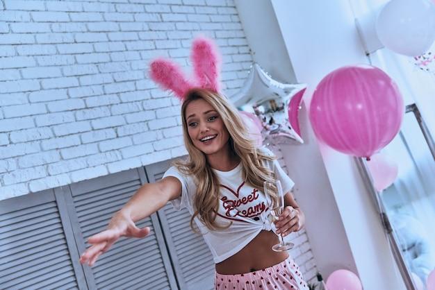 それをください!寝室に立っている間身振りと笑顔のパジャマで美しい若い女性