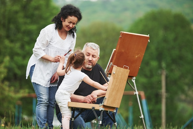 Give me that brush. grandmother and grandfather have fun outdoors with granddaughter. painting conception
