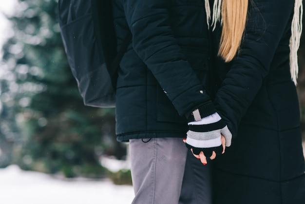 팔을 주세요. 서로의 손을 잡고 순간을 즐기는 행복한 젊은 커플의 자른 초상화. 겨울 숲 개념에 있는 사람들