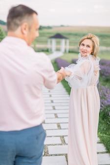 손을 내밀어 나를 따르라. 함께 몇 년 동안 사랑. 우아한 드레스를 입은 꽤 매력적인 금발의 성숙한 여인, 손을 잡고 전망대가 있는 라벤더 밭에서 야외에서 잘생긴 남자와 함께 걷고 있습니다.