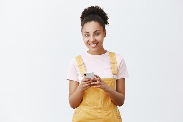 番号を教えてください。黄色のオーバーオールで魅力的な軽薄でフェミニンな浅黒い肌の若い女性の肖像画、スマートフォンを持って友人のメールを入力し、美しい笑顔で見つめています