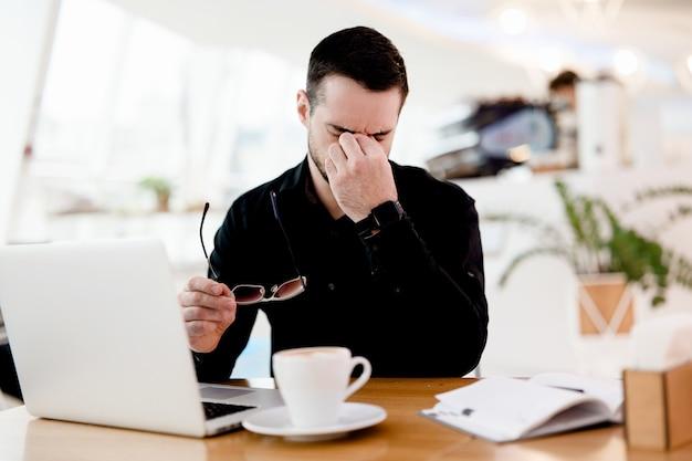 目を休ませてください!黒のシャツを着た若い疲れたフリーランサーの男性は、目の痛みと乾燥に苦しんでいます。彼はよく働きます!背景に居心地の良い喫茶店の雰囲気。テーブルの上のおいしいカプチーノのカップ。
