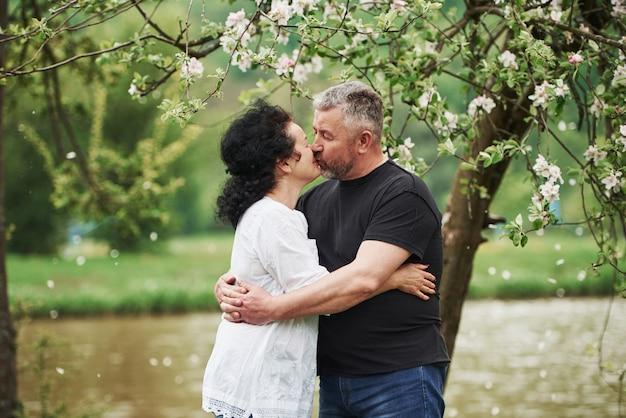 キスをします。屋外で素敵な週末を楽しんでいる陽気なカップル。良い春の天気