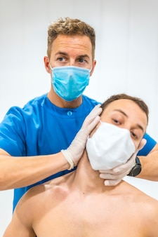 환자에게 목 마사지를 제공합니다. 코로나 바이러스 유행성 covid-19에 대한 보호 조치가 포함 된 물리 치료. 골다공증, 치료 적 chiromassage