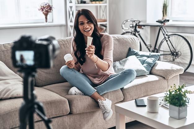 アドバイスをする。ソーシャルメディアビデオを作成し、屋内に座って笑っている女性のvlogger